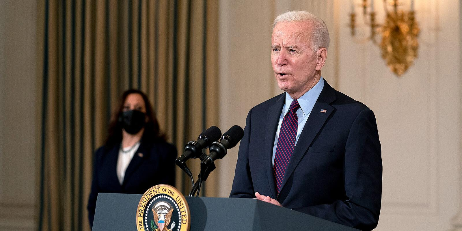 Biden speaking at podium and Karris behind him